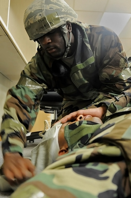 U.S. Air Force Staff Sgt. Lloyd Morris, 8th Comptroller Squadron financial services supervisor, bandages the head of U.S. Air Force Staff Sgt. Kendall Grant, 8th CPTS, for a Self-Aid Buddy Care scenario during Exercise Beverly Midnight 15-4 at Kunsan Air Base, Republic of Korea, July 17, 2015. During the five-day exercise, Airmen were tested on their ability to survive and operate while under the stress of simulated wartime activities. (U.S. Air Force photo by Senior Airman Divine Cox/Released)