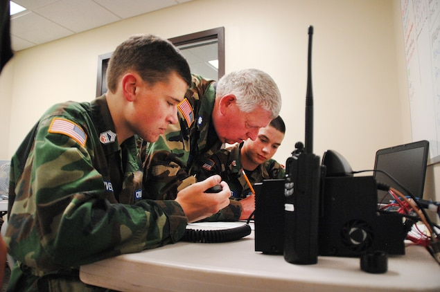 Lt. Col. James Card, (center), assistant director of communications and licensing officer, Georgia Wing Civil Air Patrol, teaches young cadets how to use communication equipment during Georgia Wing CAP's weeklong summer encampment at Marine Corps Logistics Base Albany, July 21-25.