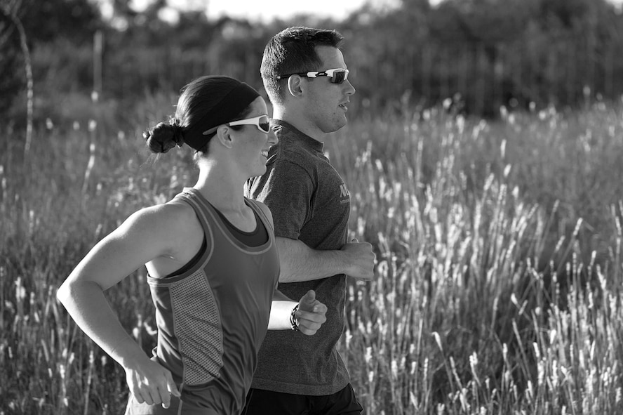 U.S. Air Force 1st Lt. Morgan K. Diglia, Sexual Assault Response Coordinator deputy, runs with her husband during a triathlon training session in San Angelo, Texas, July 22, 2015. Diglia is prepping for an olympic triathlon, which includes a 1.5km swim, 40km bike ride, and a 10km run. (U.S. Air Force photo by Staff Sgt. Michael Smith/Released)