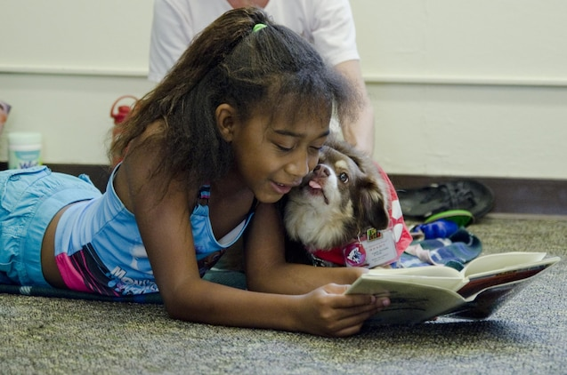 Brianna Torbert, 10, gets affection from therapy dog Molly, an 8-year-old miniature Australian shepherd during the Reading to Dogs event at the base library, July 22, 2015. Molly is certified with the Reading Education Assistance Dogs program from Intermountain Therapy Animals, a nonprofit organization based in Salt Lake City. Molly, and her handler, Angie McGaffin, a board member of nonprofit organization, Tails of Aloha, visit various locations on the island to provide therapy for people. (U.S. Marine Corps photo by Kristen Wong/Released)