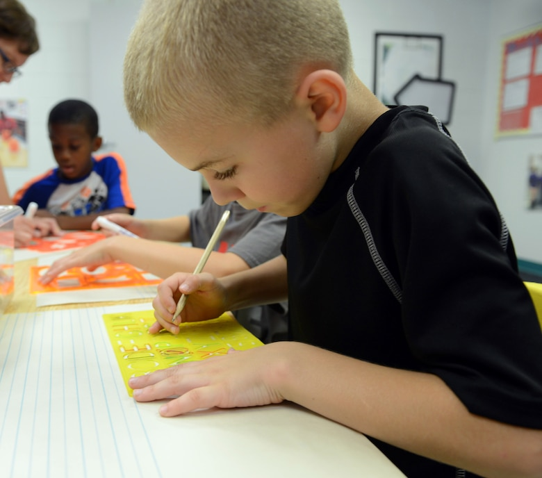 Eight-year-old Aaron Franklin creates artwork with a group of students at the center. . (U.S. Air Force photo by Tommie Horton)
