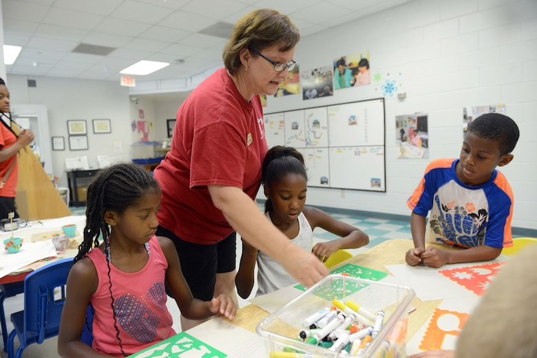 Marcia Gill, Robins Youth Center program assistant, leads activities for a group of youth at the facility. Beginning Aug. 3, the center will offer before-and after-school care for children between 5 and 12 years of age. (U.S. Air Force photo by Tommie Horton)