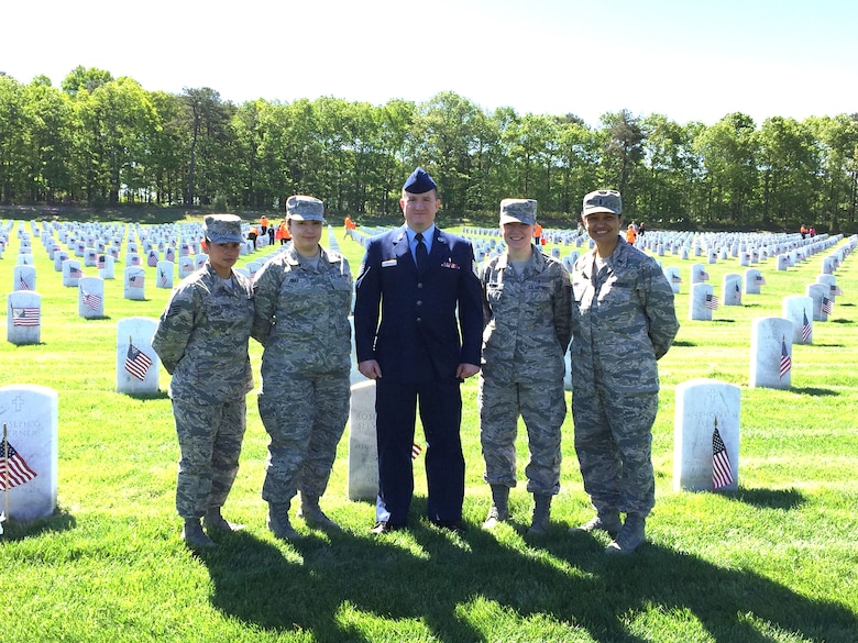 106th Medical Group members and more than 6,700 people decorate gravestones with small American flags at Calverton National Cemetery on Memorial Day weekend, May 23rd 2015.
