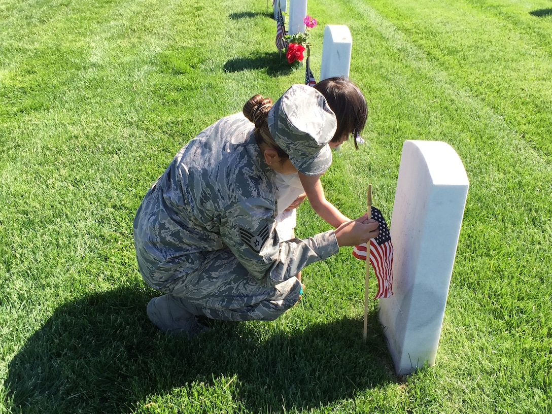 106th Rescue Wing medical technician Staff Sgt. Rendal-Sestoso and her daughter placing a small American flag by a gravestone at Calverton National Cemetery in commemoration of Memorial Day.