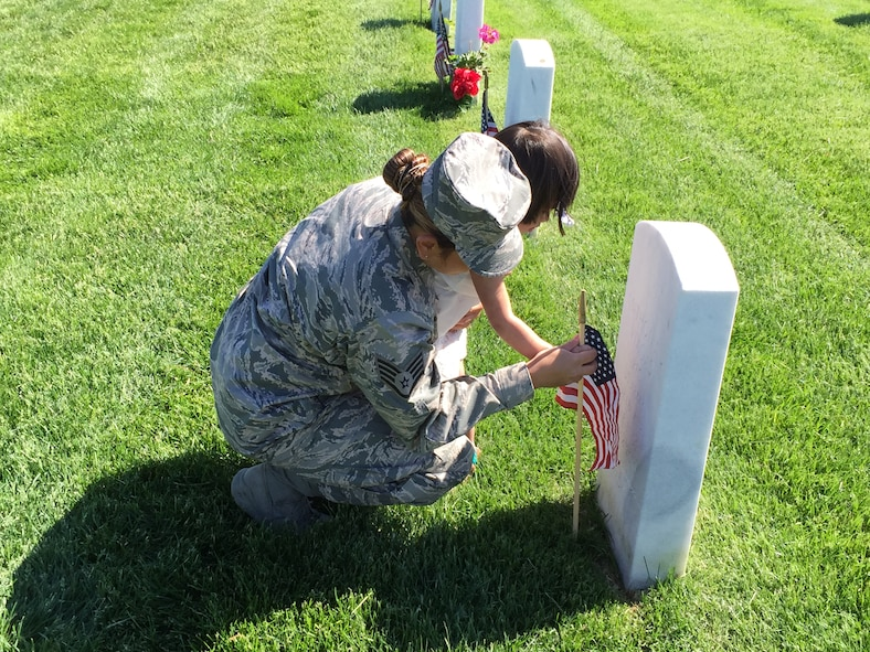 106th Rescue Wing medical technician Staff Sgt. Rendal-Sestoso and her daughter placing a small American flag by a gravestone at Calverton National Cemetery in commemoration of Memorial Day.  106th Rescue Wing members and more than 6,700 people decorated gravestones with small American flags at Calverton National Cemetery on Memorial Day weekend, May 23rd 2015.