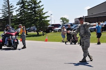 Senior Airman Nathan McLallen, 914th Security Forces Squadron, directs vehicular and pedestrian traffic during the 2015 Thunder of Niagara Air Show on July 19, 2015. More than 200 security personnel were used at traffic control points and entrances, as well as, providing public safety. (U.S. Air Force photo by Master Sgt. Kevin Nichols)