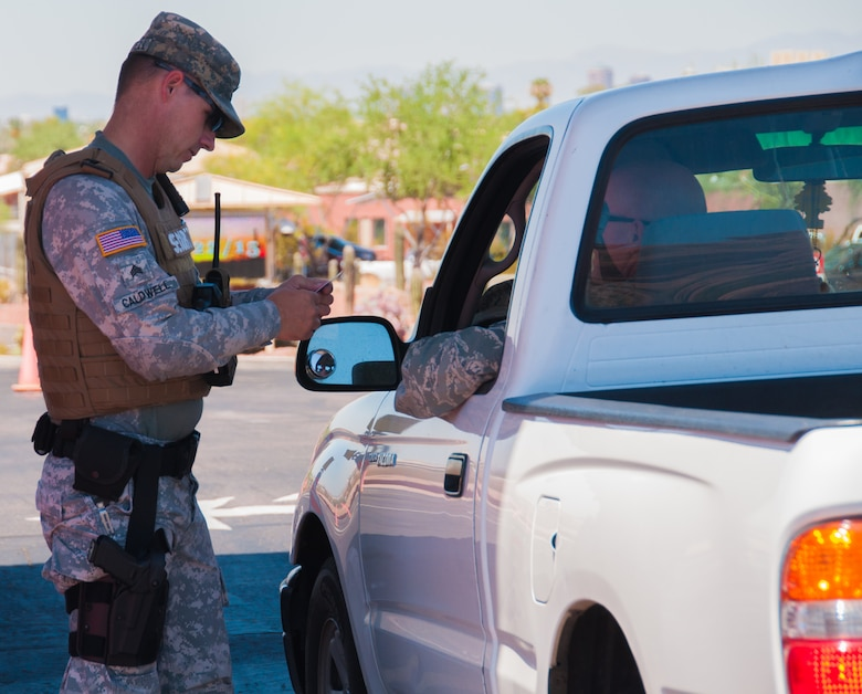 A member of the Arizona Army National Guard's security force checks identification at the main gate of Papago Park Military Reservation, here July 22. Arizona is among several states that have recently announced it will arm service members on Guard instillations and facilities across the state under the direction of an executive order signed by Gov. Doug Ducey. (U.S. Army National Guard Photo by Spc. Wes Parrell)