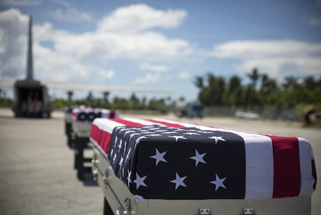 Caskets carrying the remains of approximately 36 Marines rest on the tarmac, July 25, 2015, in Tarawa, Kiribati, before a repatriation ceremony. The remains were honored during the ceremony and loaded onto a C-130J Hercules aircraft for their return home to the United States where they will be identified and laid to rest in their final resting place.