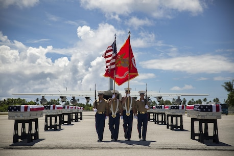 A 3rd Marine Regiment color guard takes its place, July 25, 2015, during a repatriation ceremony in Tarawa, Kiribati. The ceremony honored the remains of approximately 36 Marines who fought and died during the Battle of Tarawa during World War II, and were loaded onto a C-130J Hercules aircraft to be transported back home to the United States.