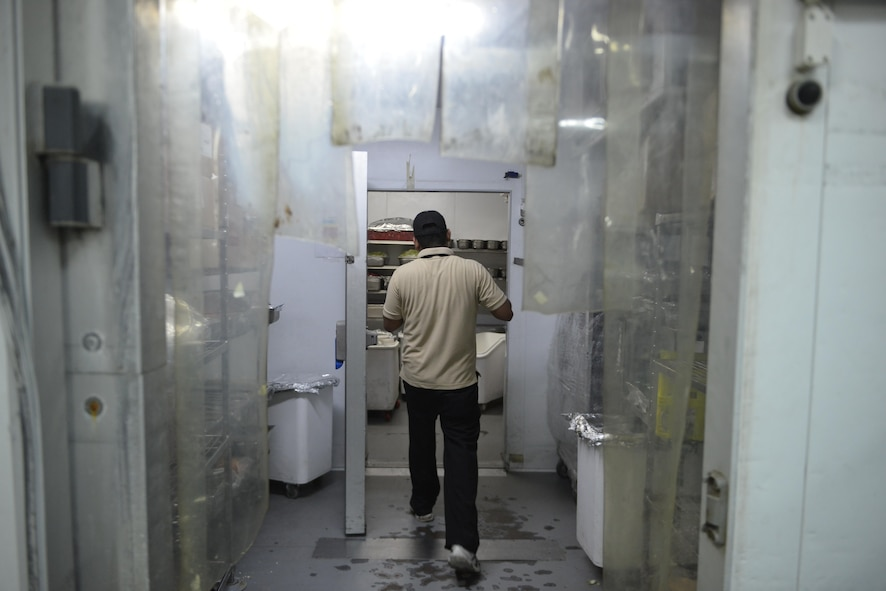 A dining facility member stores a pan of food in the industrial walk-in freezer at the Independence Dining Facility at Al Udeid Air Base, Qatar July 21, 2015. (U.S. Air Force photo/Staff Sgt. Alexandre Montes)