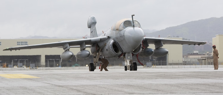 A Marine Tactical Electronic Warfare Squadron 2 (VMAQ 2) EA-6B, stops for a brake check before pulling into the hot refueling pits for the first time aboard Marine Corps Air Station Iwakuni, Japan, July 22, 2015. Prowlers have a wingspan of 53 feet, but the hot pits only accommodate for a wingspan of 50 feet. U.S. Naval Air System Command approved a waiver making it possible for the Prowlers to use the hot pits after deeming the pits safe with enough clearance to host a Prowler.