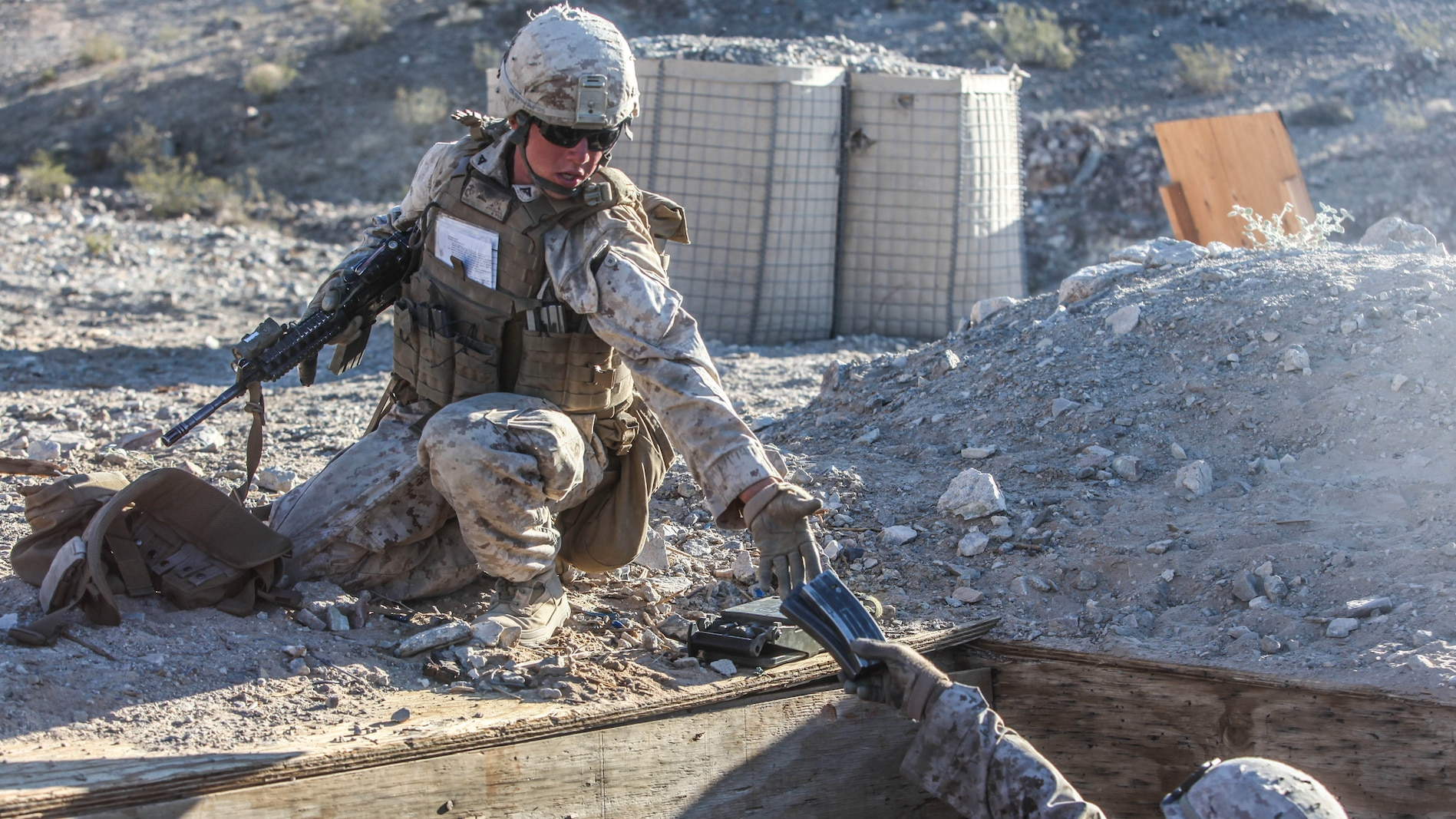 Two Marines with 1st Platoon, Company C, 1st Battalion, 7th Marines, distribute ammunition during platoon attack drills, July 24, aboard Marine Corps Air Ground Combat Center Twentynine Palms, Calif. Training began for the Marines of Company C with a combined arms fire and maneuver exercise as part of their Integrated Training Exercise in preparation for their upcoming deployment with Special Purpose Marine Corps Air Ground Task Force Crisis Response Central Command 16.1 scheduled to depart later this year.