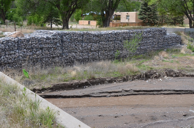 As Climate Changes, Santa Clara Strives To Become Resilient To Worsening Fires, Floods: Rock-filled gabion baskets line the Santa Clara Creek where it flows under a state road in Santa Clara Pueblo. High flows of water from the burn scar in Santa Clara Canyon and the watershed of Santa Clara Creek threaten the village, and the mesh-and-rock gabion structures assist with flood control. Courtesy Elizabeth Lockyear/U.S. Army Corps of Engineers, Albuquerque District