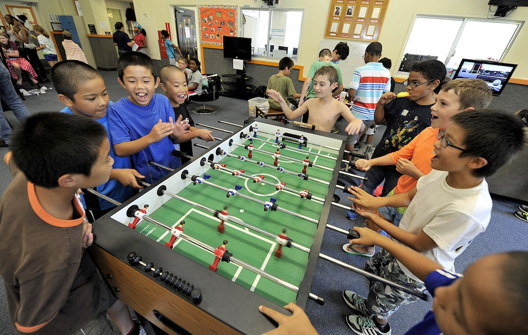 Japanese children from Chatan Town elementary schools play football with American children at the Youth Center during a visit on Kadena Air Base, Japan, July 23, 2015. The visit allowed American and Japanese children to exchange culture by playing games and eating lunch together. (U.S. Air Force photo by Naoto Anazawa/Released)