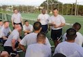 U.S. Air Force Chief Master Sgt. Matthew Caruso, U.S. Air Force Special Operations Command command chief, speaks to Airmen from the 353rd Special Operations Maintenance Squadron following a physical training session with the squadron on Kadena Air Base, Japan, July 21, 2015. Caruso joined the squadron for a physical training session and ended the gathering with words about professionalism, resilience and pride. He also presented challenge coins to highlight the efforts of outstanding performers within the unit. (U.S. Air Force photo by Airman 1st Class John Linzmeier)