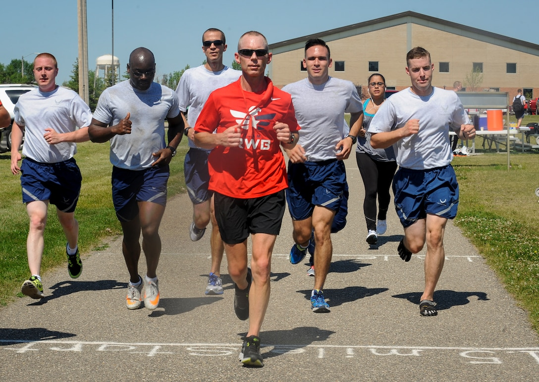 Chief Master Sgt. Geoff Weimer, 5th Bomb Wing command chief, leads a group of Airmen on the 50th mile of a 52 mile run at Minot Air Force Base, N.D., July 24, 2015. To prepare for the event, Weimer made distance adjustments to his regular running routine and factored in fatigue and physical stress. (U.S. Air Force photo/Senior Airman Stephanie Morris)