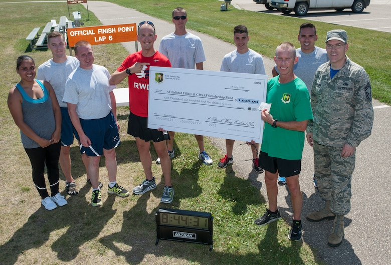 Chief Master Sgt. Geoff Weimer, 5th Bomb Wing command chief, is presented a check at the outdoor track finish line after running 52 miles at Minot Air Force Base, N.D., July 24, 2015. Weimer completed the run to support the Air Force Enlisted Village and Chief Master Sergeant Scholarship Fund and was able to raise $1,733.60. (U.S. Air Force photo/Senior Airman Stephanie Morris)