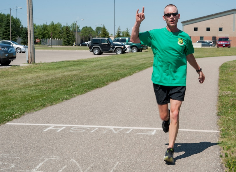 Chief Master Sgt. Geoff Weimer, 5th Bomb Wing command chief, crosses the finish line after running 52 miles at Minot Air Force Base, N.D, July 24, 2015. Weimer completed the run to support the Air Force Enlisted Village and Chief Master Sergeant Scholarship Fund. (U.S. Air Force photo/Senior Airman Stephanie Morris)
