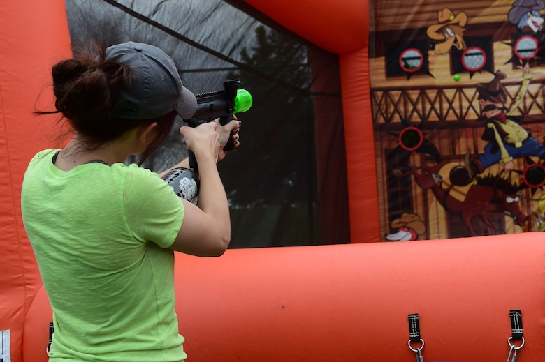 A girl takes aim at targets during FunFest July 24, 2015, at Buckley Air Force Base, Colo. FunFest is an annual base-wide event that includes family- friendly games and activities, community involvement and local business sponsors. (U.S. Air Force photo by Airman 1st Class Luke W. Nowakowski/Released)