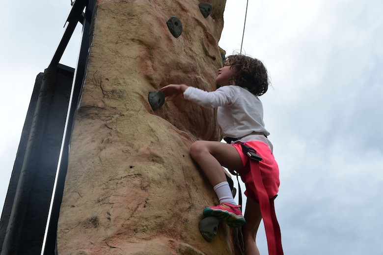 A girl climbs a rock wall during FunFest July 24, 2015, at Buckley Air Force Base, Colo. FunFest is an annual base-wide event that includes family-friendly games and activities, community involvement and local business sponsors. (U.S. Air Force photo by Airman 1st Class Luke W. Nowakowski/Released)