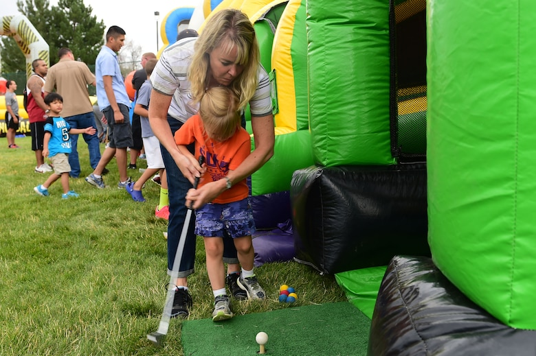 A mother helps her daughter hit a golf ball during FunFest July 24, 2015, at Buckley Air Force Base, Colo. FunFest is an annual base-wide event that includes family-friendly games and activities, community involvement and local business sponsors. (U.S. Air Force photo by Airman 1st Class Luke W. Nowakowski/Released)