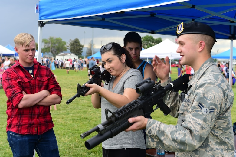 A member of the 460th Security Forces Squadron demonstrates how to use a weapon during FunFest July 24, 2015, at Buckley Air Force Base, Colo. FunFest is an annual base-wide event that includes family-friendly games and activities, community involvement and local business sponsors. (U.S. Air Force photo by Airman 1st Class Luke W. Nowakowski/Released)