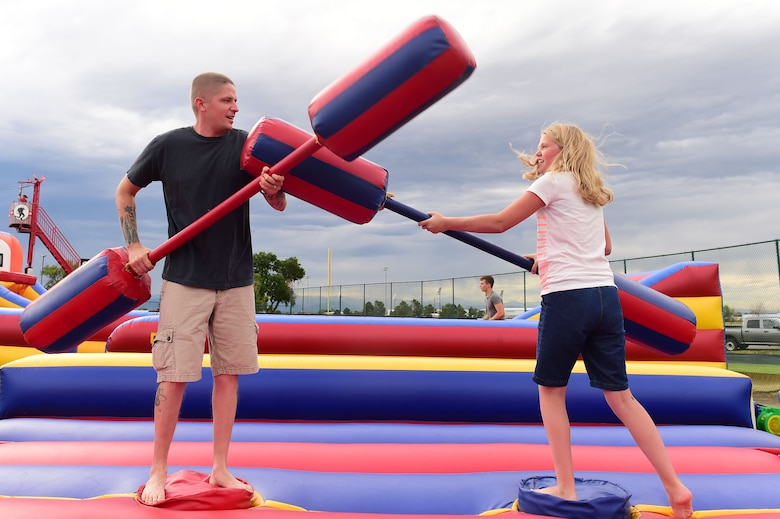 A father and daughter joust during FunFest July 24, 2015, at Buckley Air Force Base, Colo. FunFest is an annual base-wide event that includes family-friendly games and activities, community involvement and local business sponsors. (U.S. Air Force photo by Airman 1st Class Luke W. Nowakowski/Released)