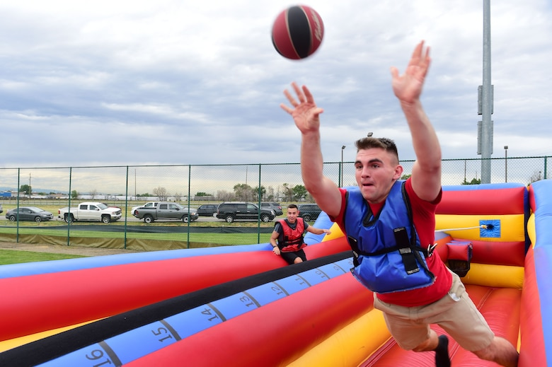 Airman 1st Class Dakota Osborne, 2nd Space Warning Squadron space systems operator, tries to make a basket during FunFest July 24, 2015, at Buckley Air Force Base, Colo. FunFest is an annual base-wide event that includes family-friendly games and activities, community involvement and local business sponsors. (U.S. Air Force photo by Airman 1st Class Luke W. Nowakowski/Released)