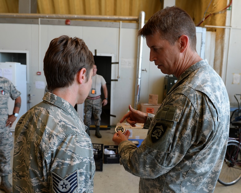 U.S. National Guard Maj. Gen. Daniel Hokanson, Oregon National Guard Adjutant General, describes his coin to an Airman that he will coin during a base tour at Campia Turzii, Romania, July 22, 2015. Hokanson visited the 123rd Expeditionary Fighter Squadron during their theater security package deployment to Campia Turzii. The visit allowed Hokanson to pass along information from home, answer questions and learn more about their mission in Romania. More than 200 Airmen from the 142nd Fighter Wing, Oregon Air National Guard, Portland, Oregon, are training with the Romanian air force as part of a European theater security package of F-15C Eagles deployed to Romania. (U.S. Air Force Senior Airman Dylan Nuckolls/Released)