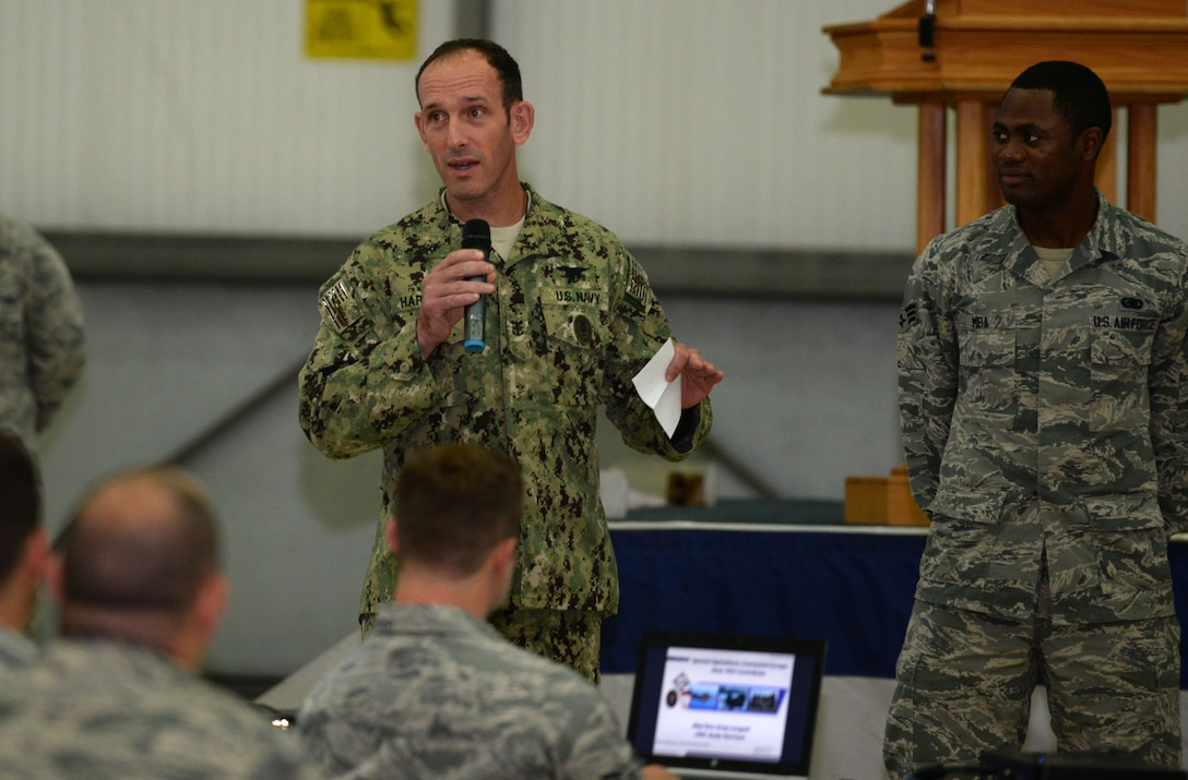 From left, U.S. Navy Command Master Chief Petty Officer Andrew Harrison, U.S. Special Operations Command - Europe senior enlisted leader, asks Airmen quiz questions about themselves, their chain of command and home station July 23, 2015, on RAF Mildenhall, England. Harrison then used charts to explain SOCEUR chain of command and the challenges the military faces today and how the U.S. military is making European militaries stronger. (U.S. Air Force photo by Gina Randall/Released)