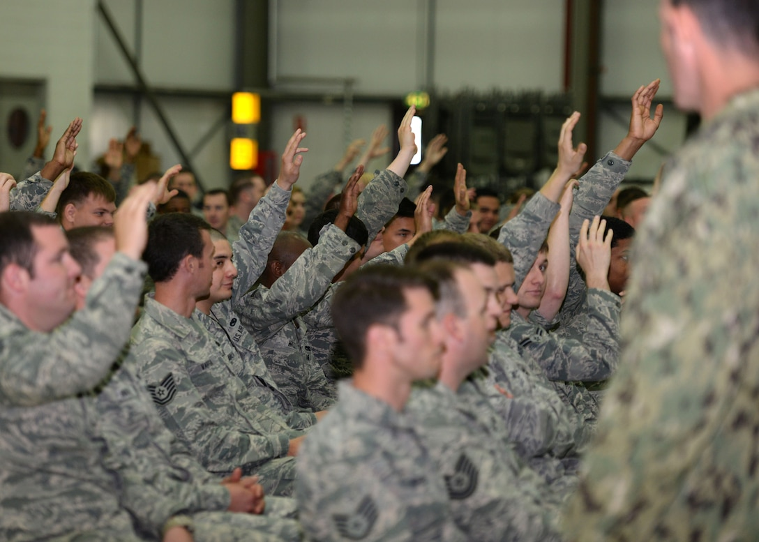 Air Commandos of the 352nd Special Operations Wing, raise their hands so U.S. Navy Command Master Chief Petty Officer Andrew Harrison, SOCEUR senior enlisted leader, can select volunteers for a discussion during an all hands call July 23, 2015, on RAF Mildenhall, England. Harrison asked the service members questions on geography, popular culture and their chain of command to get to know the team. (U.S. Air Force photo by Gina Randall/Released)