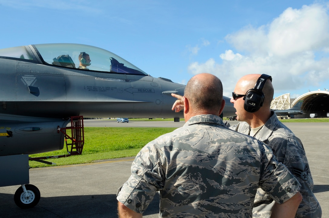 U.S. Air Force Brig. Gen Joel A. Clark, 158th Fighter Wing assistant adjutant general, speaks with Senior Airman Joe Palumbo, 158th FW fuels systems technician, during an operations check after a flight on Kadena Air Base, Japan, July 23, 2015. Air Combat Command routinely deploys fighter aircraft to the region to provide U.S. Pacific Command and Pacific Air Forces with Theater Security Packages, which help maintain a deterrent against threats to regional security and stability and demonstrate the continuing U.S. commitment to the region, the Japan-U.S. alliance and the defense of Japan. (U.S. Air Force photo by Airman 1st Class Zackary A. Henry)