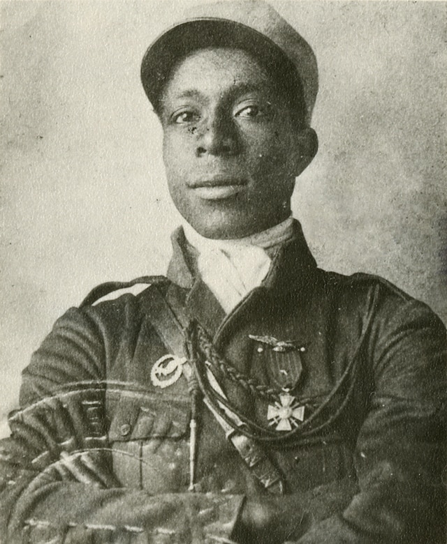 Photograph of Eugene Jacques Bullard during his flight training. The insignia on his right chest is his student pilot insignia, and the Croix de Guerre with Star he received for valor during the Battle of Verdun on his left. Just visible over the Croix de Guerre on the left are unofficial wings worn by many French pilots. (U.S. Air Force photo)