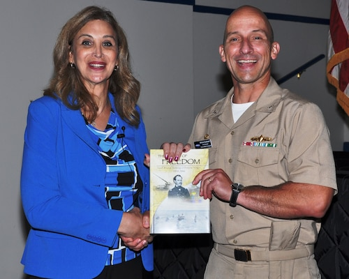 """Capt. Brian Durant, right, commander of the Naval Surface Warfare Center Dahlgren Division (NSWCDD), presents """"The Sound of Freedom"""" to Amanda Simpson, left, executive director of the Army Office of Energy Initiatives, after her presentation at the LGBT Pride Month Observance at Naval Support Facility (NSF) Dahlgren on July 24."""