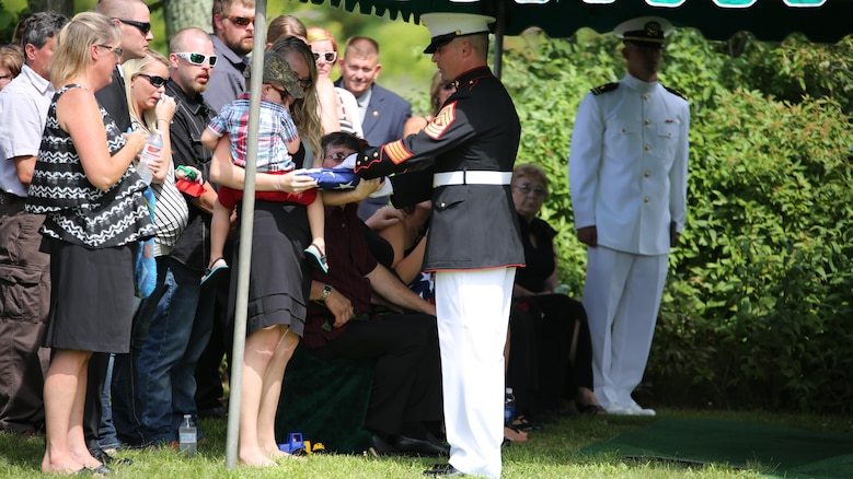 First Sgt. Timothy Dennison, the detachment first sergeant for Marine Wing Support Squadron 471, 4th Marine Aircraft Wing, presents a folded flag to the son of Sgt. Carson Holmquist, a motor transport maintenance chief with Battery M, 3rd Battalion, 14th Marine Regiment, 4th Marine Division, Marine Forces Reserve, during his funeral July 25, 2015 in Grantsburg, Wisconsin. Holmquist, along with three other Marines and a sailor, was killed in an attack at the Naval Operation Support Center and Marine Corps Reserve Center in Chattanooga, Tennessee July 16, 2015. Marines, family, friends and the community of Grantsburg gathered to honor the memory and sacrifice of Holmquist and his fallen brothers-in-arms.