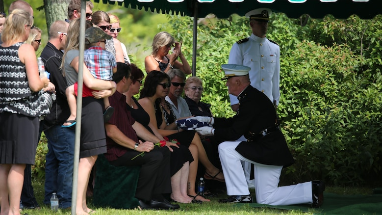 Lt. Gen. Richard P. Mills, commander of Marine Forces Reserve, presents a folded flag to the widow of Sgt. Carson Holmquist, a motor transport maintenance chief with Battery M, 3rd Battalion, 14th Marine Regiment, 4th Marine Division, Marine Forces Reserve, during his funeral July 25, 2015 in Grantsburg, Wisconsin. Holmquist, along with three other Marines and a sailor, was killed in an attack at the Naval Operation Support Center and Marine Corps Reserve Center in Chattanooga, Tennesee July 16, 2015. Marines, family, friends and the community of Grantsburg gathered to honor the memory and sacrifice of Holmquist and his fallen brothers-in-arms.