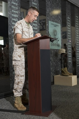 U.S. Marine Corps Capt. Caleb Eames, Public Affairs Officer for Okinawa, Japan, gives the opening benediction during a memorial service and induction ceremony in the Hall of Heroes at the Defense Information School on Fort George G. Meade, Md., July 27, 2015. The ceremony was in honor of U.S. Marine Corps Cpl. Sara A. Medina and Lance Cpl. Jacob A. Hug, combat photographers who were killed during earthquake relief operations in Nepal, May 12, 2015. (DoD photo by Shane Keller/Released)