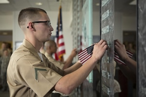 U.S. Marine Corps Pfc. Andrew Piehler, a Marine awaiting training, unveils a name placard during a memorial service and induction ceremony in the Hall of Heroes at the Defense Information School on Fort George G. Meade, Md., July 27, 2015. The ceremony was in honor of U.S. Marine Corps Cpl. Sara A. Medina and Lance Cpl. Jacob A. Hug, combat photographers who were killed during earthquake relief operations in Nepal, May 12, 2015. (DoD photo by Shane Keller/Released)