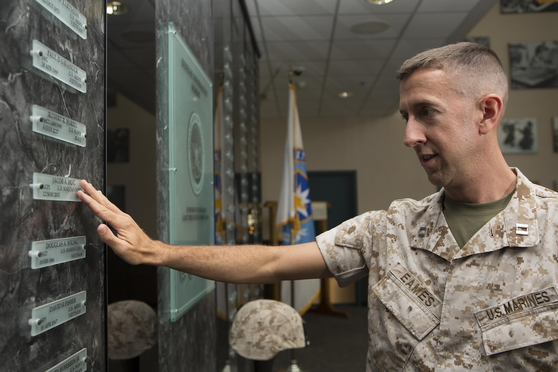 U.S. Marine Corps Capt. Caleb Eames, public affairs officer for Okinawa, Japan, touches the name tag of U.S. Marine Corps Lance Cpl. Jacob A. Hug after a memorial service and induction ceremony in the Hall of Heroes at the Defense Information School on Fort George G. Meade, Md., July 27, 2015. The ceremony was in honor of U.S. Marine Corps Cpl. Sara A. Medina and Hug, combat photographers who were killed during earthquake relief operations in Nepal, May 12, 2015. (DoD photo by Shane Keller/Released)