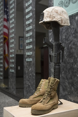 A battle cross sits on display in the Hall of Heroes for U.S. Marine Corps Cpl. Sara A. Medina and Lance Cpl. Jacob A. Hug at the Defense Information School on Fort George G. Meade, Md., July 27, 2015. Medina and Hug, combat photographers, were killed during earthquake relief operations in Nepal, May 12, 2015. (DoD photo by Shane Keller/Released)