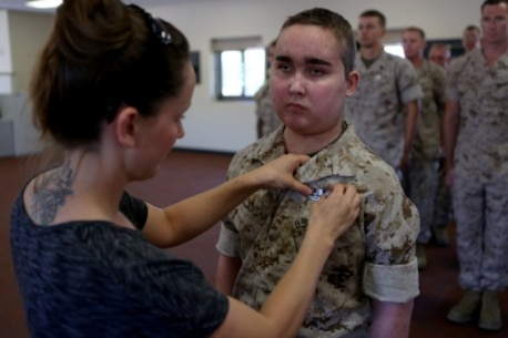 James Gallant, a young man diagnosed with brain cancer, is pinned with an Explosive Ordnance Disposal technician badge by his mother Sarah Silverstein, before Marines of 1st EOD Company, 1st Marine Logistics Group, aboard Camp Pendleton, Calif., July 25, 2015. Collaborating with the Make-A-Wish Foundation, 1st EOD helped James experience what being an EOD technician is like by giving him a tour through their library of ordnance and EOD tools, teaching him to operate the TALON bomb disposing robot and presenting him with his own desert utilities and EOD badge.