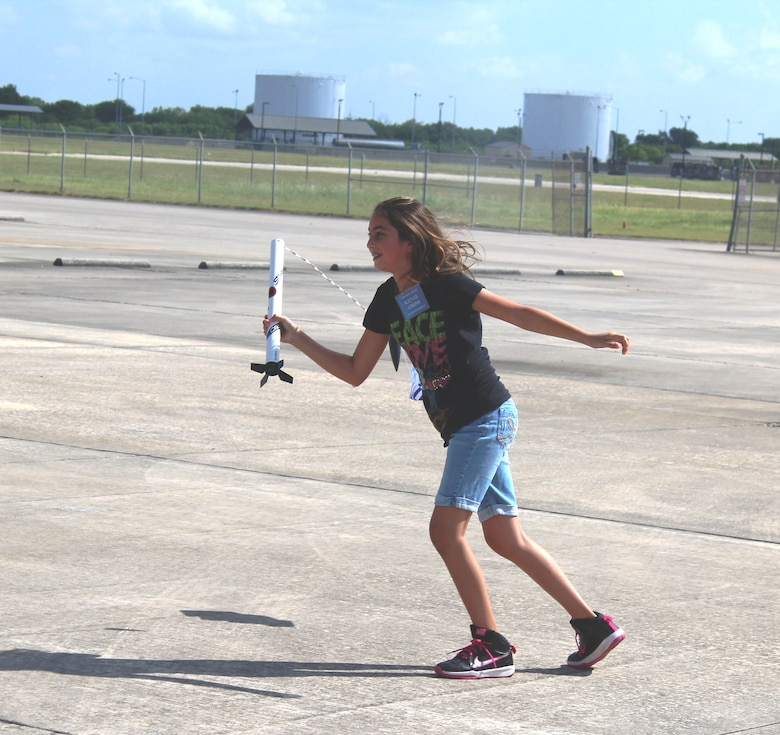 Kayla Adkins, daughter of Master Sgt. Helen Adkins, a training and logistics readiness manager at the 149th Fighter Training Wing, catches her model rocket after a successful launch on the final morning of her week-long class at DoD STARBASE-Kellyat Joint Base San Antonio-Lackland, Texas on July 17, 2015. Kayla, along with 19 other students, successfully launched her rocket later on that morning. (U.S. Air Force photo/Tech. Sgt. Carlos J. Trevino)