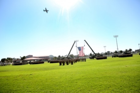 A C-130 aircraft flies by during the 1st Marine Logistics Group Change of Command Ceremony aboard Camp Pendleton, Calif., July 24, 2015. Major Gen. Vincent A. Coglianese relinquished command of 1st MLG to Brig. Gen. David A. Ottignon during a change of command ceremony at the 11 Area Parade Field, July, 24, 2015. The ceremony included the passing of the 1st MLG colors, remarks from the incoming and outgoing commanders, performances by the 1st Marine Division Band, a C-130 flyover and static displays depicting the various aspects of the MLG.