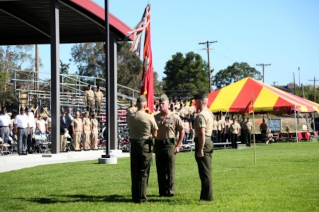 Major Gen. Vincent A. Coglianese passes the group colors to Brig. Gen. David A. Ottignon during the 1st Marine Logistics Group Change of Command Ceremony aboard Camp Pendleton, Calif., July 24, 2015. Coglianese relinquished command of 1st MLG to Ottignon during a change of command ceremony at the 11 Area Parade Field, July, 24, 2015. The ceremony included the passing of the 1st MLG colors, remarks from the incoming and outgoing commanders, performances by the 1st Marine Division Band, a C-130 flyover and static displays depicting the various aspects of the MLG.