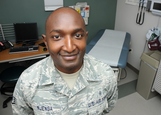 """Staff Sgt. Johnson Njenga, 21st Medical Squadron NCO-in charge of Family Health and Kenya native, poses for a photo in an exam room at the base clinic at Schriever  Air Force Base, Colorado, Tuesday, July 28, 2015, for the """"I am Schriever"""" diversity campaign. This campaign aims to recognize the diversity on Schriever and highlight how it makes us stronger. (U.S. Air Force photo/Staff Sgt. Debbie Lockhart)"""