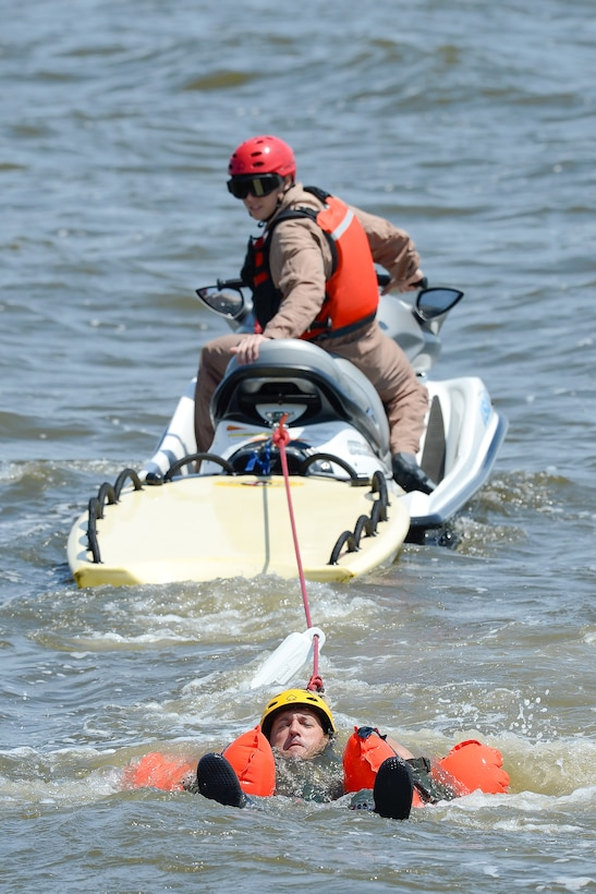 Water survival refresher trainee, Master Sgt. Joshua Mal, 3d Airlift Squadron C-17A Globemaster III loadmaster, keeps his head above water as Staff Sgt. Adam Ellerd, 436th Operations Support Squadron Survival, Evasion, Resistance and Escape Operations NCO in charge, looks over his shoulder from a personal watercraft to see when and if Mal successfully releases from his harness July 17, 2015, near Dover Air Force Base, Del. Mal and other students had to find and release their torso harness fittings while being towed through the water to simulate being dragged by their canopy after landing in water. (U.S. Air Force photo/Greg L. Davis)