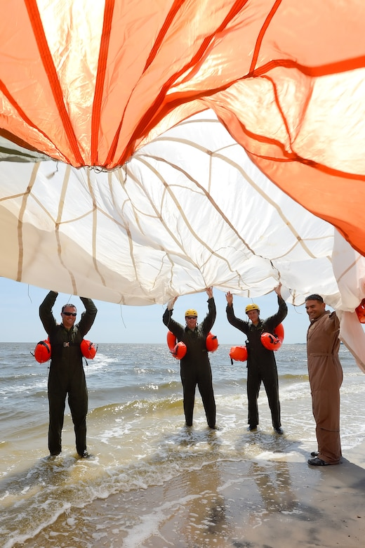 Technical Sgt. Joseph Monreal, 436th Operations Support Squadron Survival, Evasion, Resistance and Escape Operations flight chief, right, and water survival training students hold a C-9 round parachute canopy with orange and white panels above their heads as they prepare to walk it in to the water of the Delaware Bay without it becoming tangled during aircrew water survival refresher training July 17, 2015, near Dover Air Force Base, Del. Once the canopy was in the water each student had a chance to gain confidence in their ability to get out from under a water soaked canopy by following a seam to the edges. (U.S. Air Force photo/Greg L. Davis))
