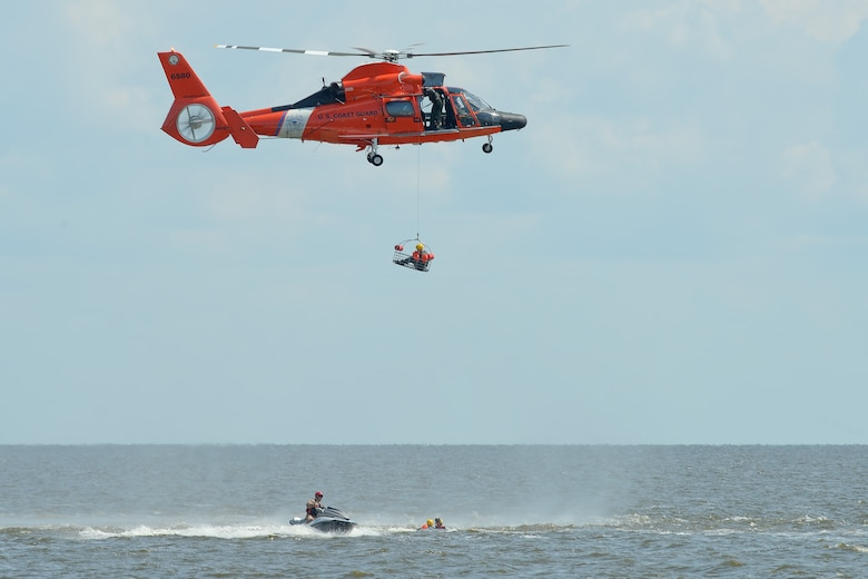 A U.S. Coast Guard HH-65D Dolphin helicopter practices hoisting U.S. Air Force aircrew members while a Coast Guard rescue swimmer prepares the next student, who was just moved in to position by Staff Sgt. Adam Ellerd, 436th Operations Support Squadron Survival, Evasion, Resistance and Escape Operations NCO in charge, using a personal watercraft July 17, 2015, near Dover Air Force Base, Del. The HH-65D is based at Coast Guard Air Station Atlantic City, N.J. (U.S. Air Force photo/Greg L. Davis)