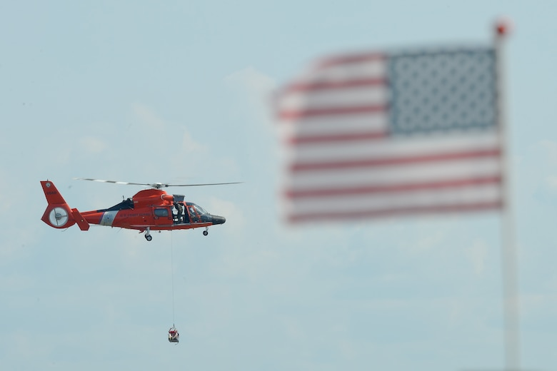 An American flag flying on the beach partially frames a U.S. Coast Guard HH-65D Dolphin helicopter that practices hoisting members of the 436th and 512th Airlift Wings from the Delaware Bay during water survival refresher training conducted by the 436th Operations Support Squadron Survival, Evasion, Resistance and Escape Operations July 17, 2015, near Dover Air Force Base, Del.  Team Dover C-5M Super Galaxy and C-17A Globemaster III aircrew are required to undergo refresher training every three years. (U.S. Air Force photo/Greg L. Davis)