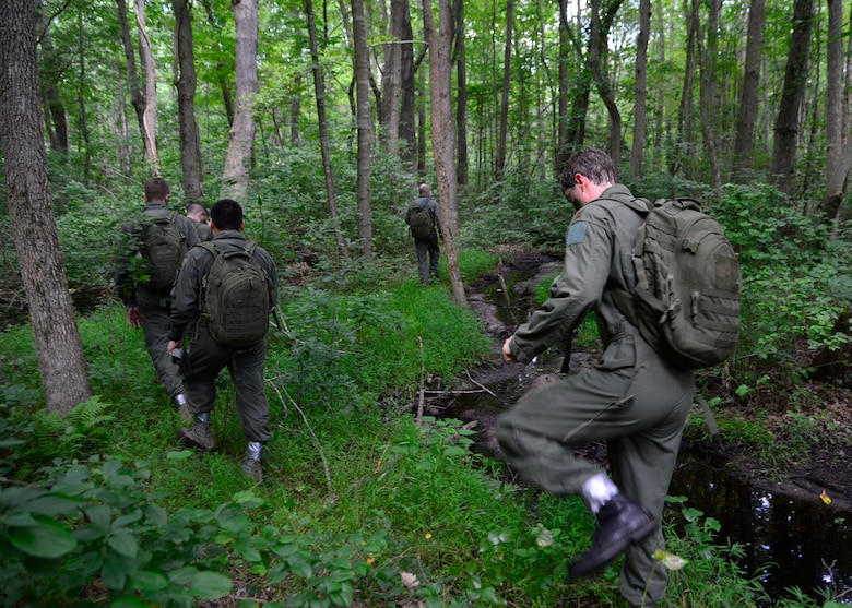 An aircrew follows a creek while navigating and evading enemy forces during a combat survival training exercise July 16, 2015, at the Blackbird State Forest near Smyrna, Del. The aircrew had to navigate through several miles of forest while trying to evade enemy forces to be rescued by friendly personnel. (U.S. Air Force photo/Airman 1st Class William Johnson)